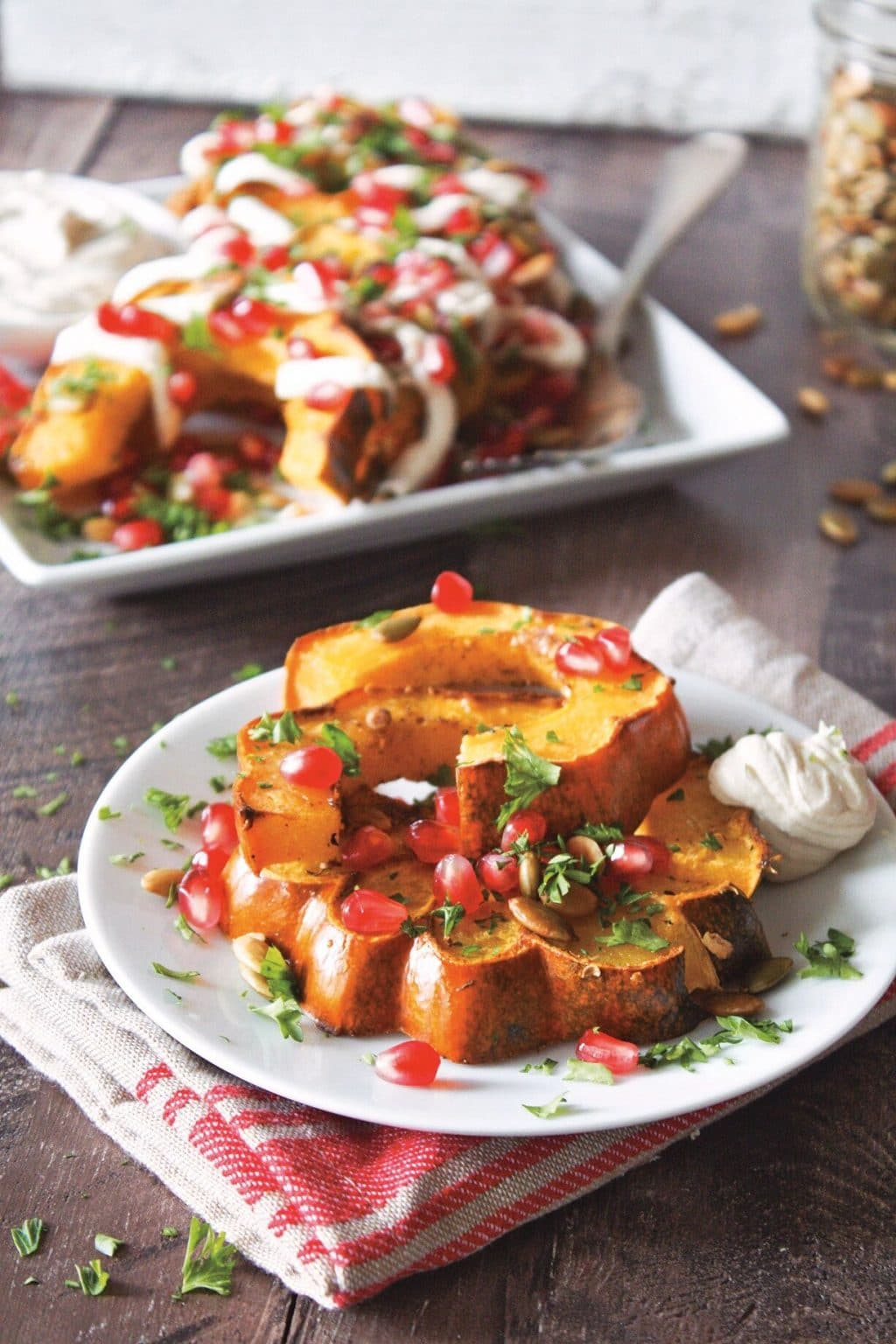 Roasted butternut squash with garam masala on a white plate with a platter of the recipe in the background