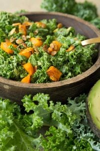 Kale and roasted squash salad in a wood bowl with a gold fork in the bowl and kale leaves and a sliver of avocado next to the bowl