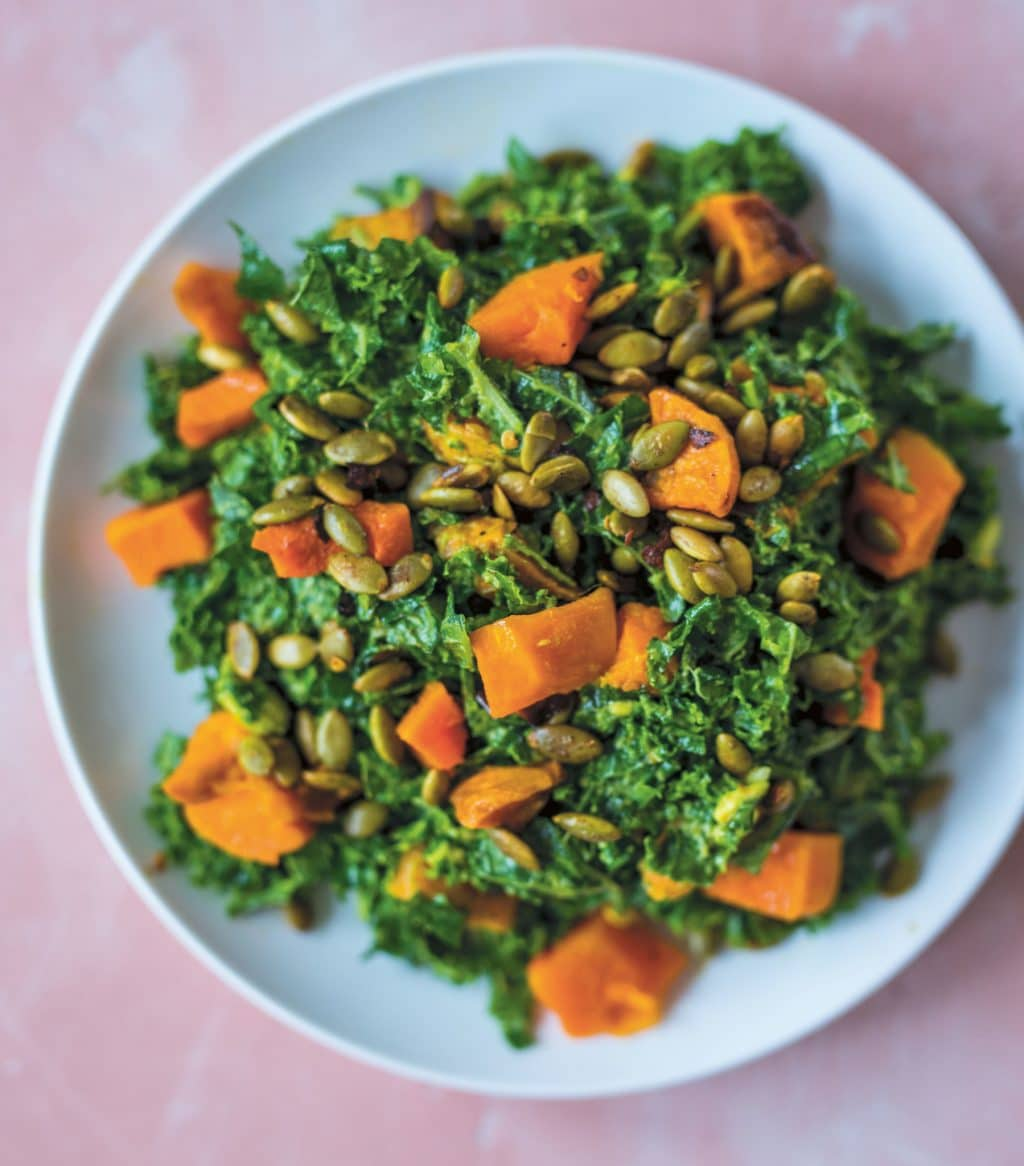 Avocado Kale Salad with Butternut Squash on a blue dish with a pink background
