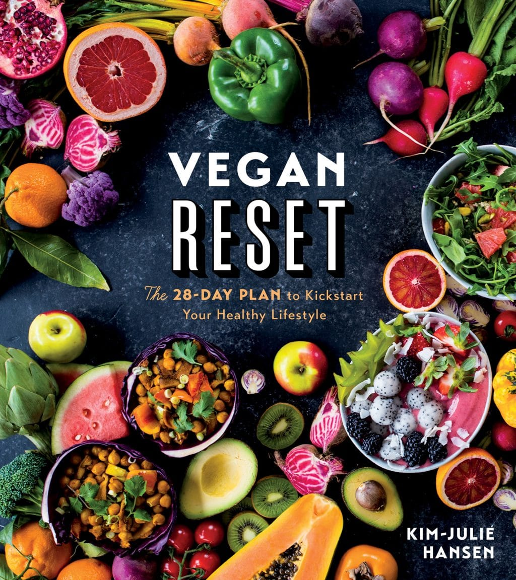 The cover of the cookbook, Vegan Reset. A dark background with vibrant fruit and bowls of vegan food