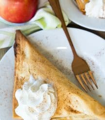 A vegan apple turnover with a dollop of whipped cream on top on a white plate with a gold fork on it and a red apple next to the plate
