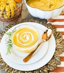 Hannah sweet potato and pumpkin bisque in a clear mug with cashew cream rosemary and a copper basket with an acorn squash