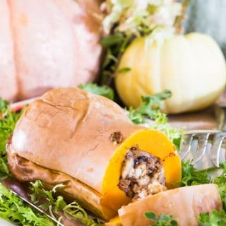 Stuffed butternut squash filled with stuffing on a bed of greens on a thanksgiving table