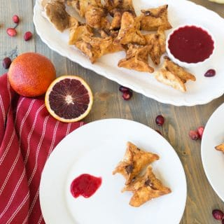 Ricotta and shiitake stuffed wontons with cranberry orange dipping sauce on a wooden board with white plates and a red napkin