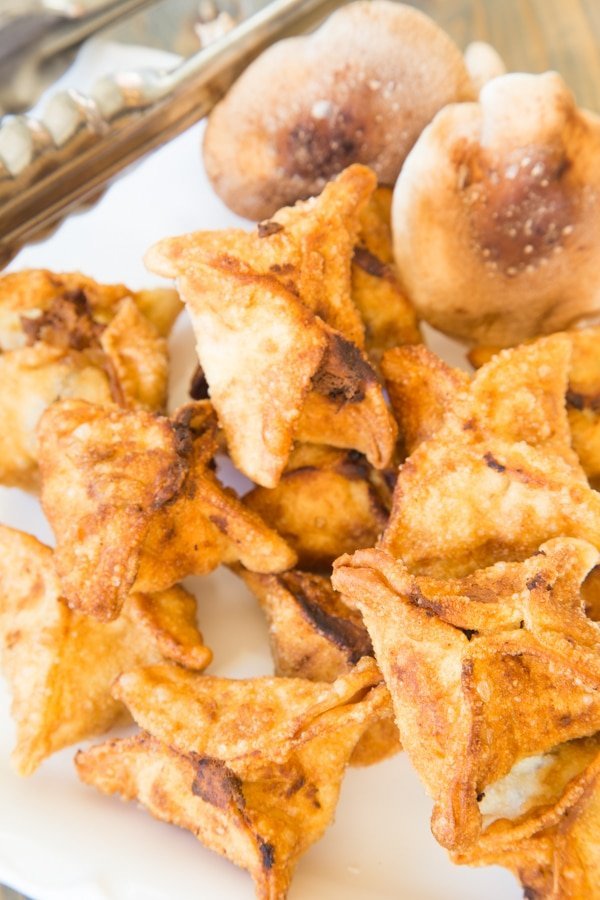 Fried ricotta and shiitake stuffed wontons on a paper towel with tongs