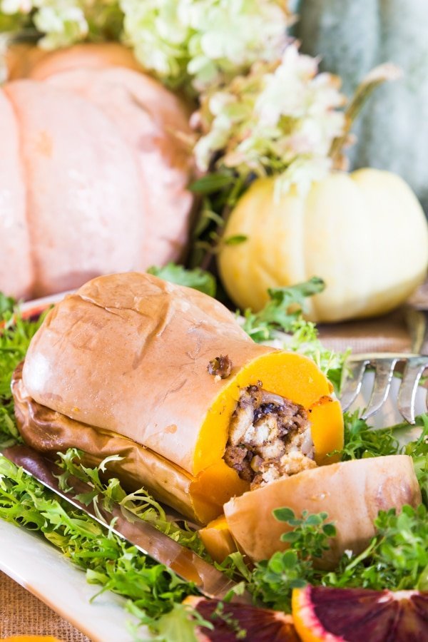 A stuffed butternut squash on a white platter with greens and large pumpkins in the background