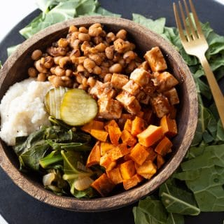A wood bowl filled with vegan barbecued vegetables on a round black serving platter and greens on the platter
