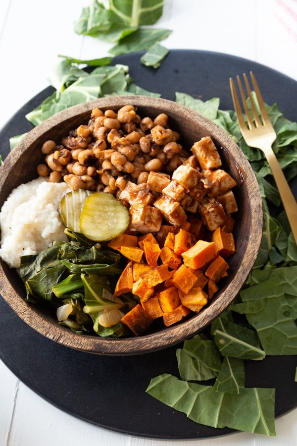 A wood bowl filled with vegan barbecued vegetables on a round black serving platter and greens on the platter created by Veganosity