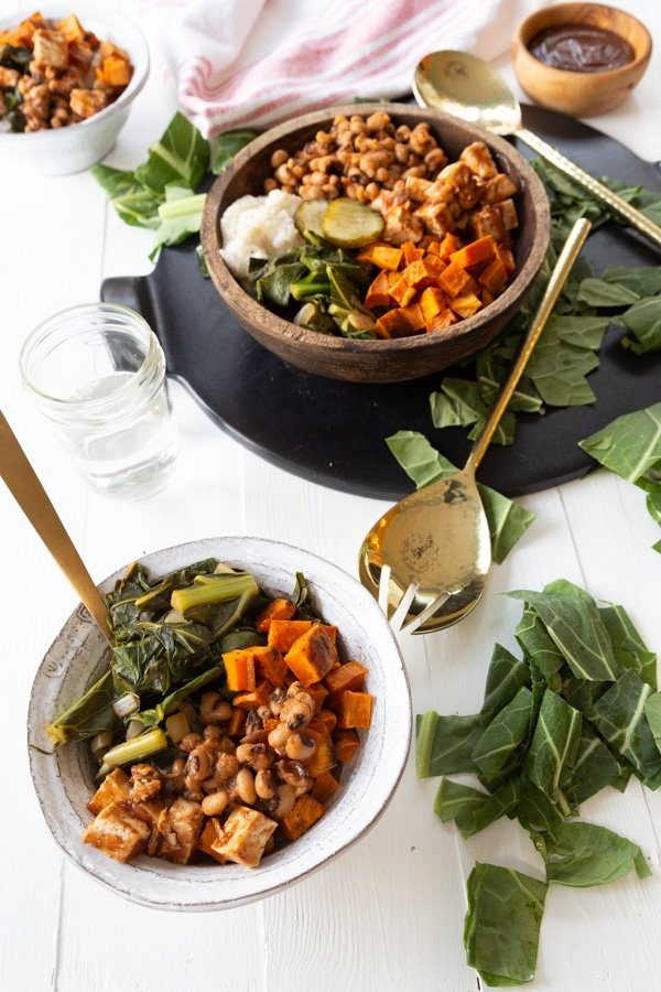 A white bowl of BBQ vegetables with a gold fork and a wood bowl of the BBQ and greens on the table