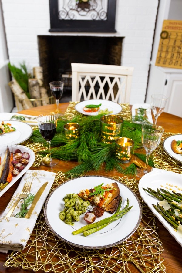 A round wood table set for Christmas with white snowflake plates, white and gold snowflake napkins, gold utensils, greens and candles in the center, and a white brick fireplace in the background
