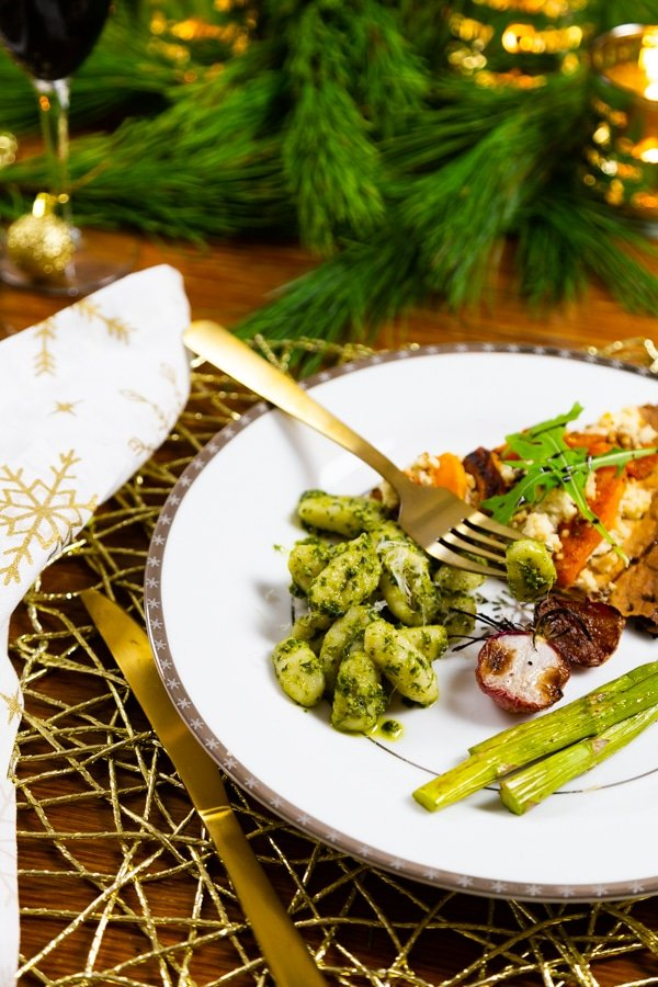 A white plate with a silver rim of snowflakes filled with pesto gnocchi, roasted asparagus and radishes, and a slice of pizza with a gold fork resting on the plate and a gold place mat and a gold knife and white and gold snowflake napkin on the side