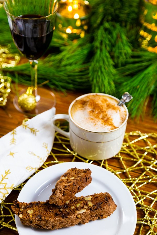 2 chocolate biscotti cookies with pecans on a white plate with a cup of coffee with foamy almond milk and cinnamon and a glass of red wine next to pine branches
