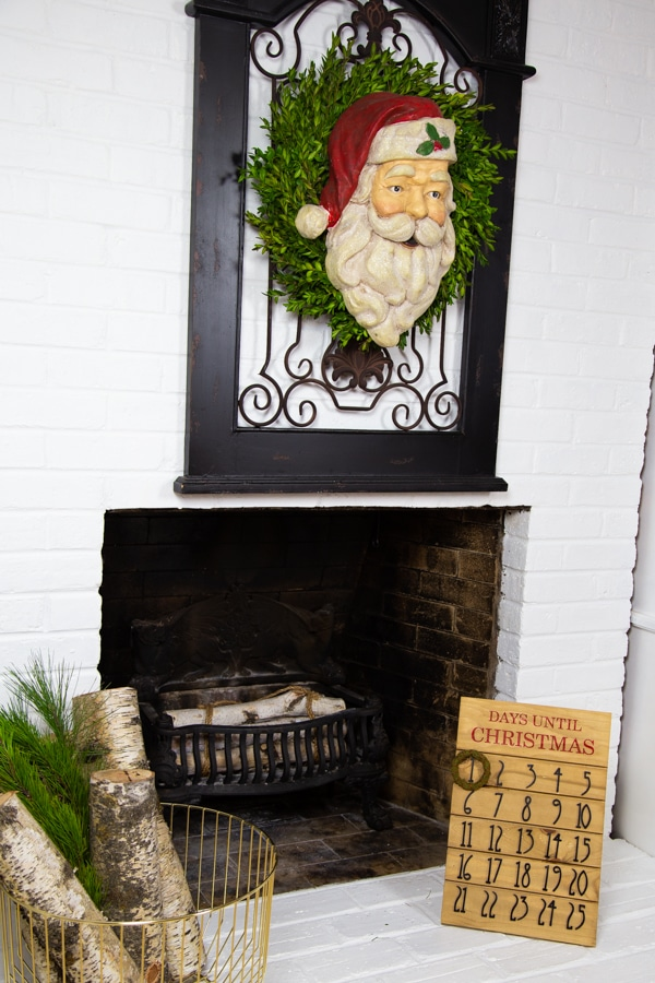 A white brick fireplace with a wood and iron gate hanging on the wall with a boxwood wreath and a Santa head, and a gold wire basket with birch logs and pine branches and a wood advent calendar on the base of the fireplace