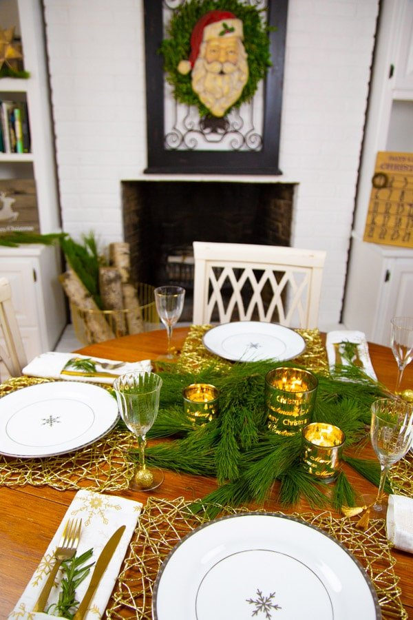 A round wood table set with white and silver snowflake plates, gold place mats, white and gold snowflake napkins, and pine branches and candles