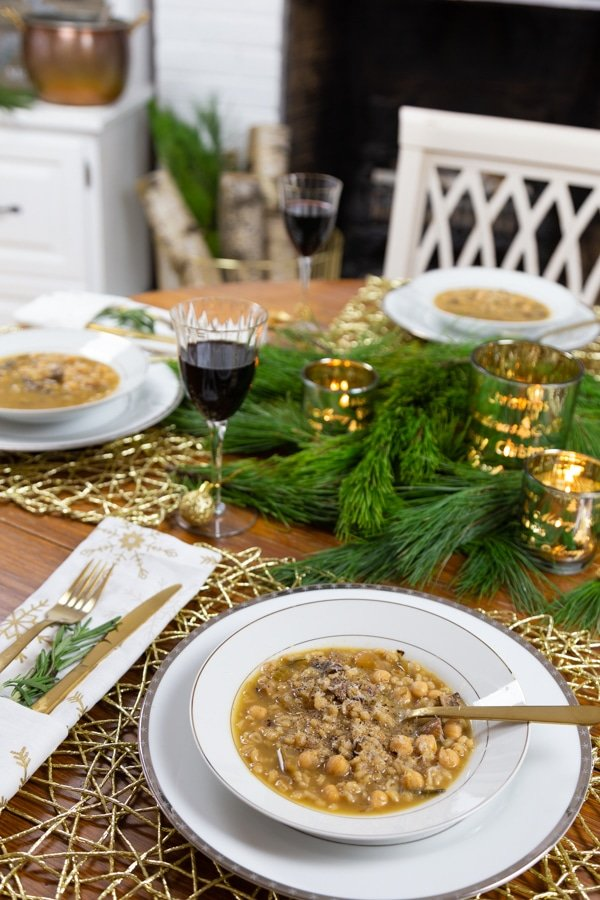 A bowl of Italian Rosemary Barley soup in a white bowl on a white plate and a gold filigree place mat with a gold spoon in the bowl of soup and pine and candles on the table