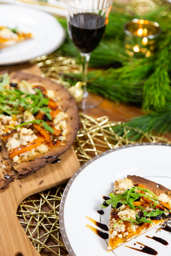 A slice of butternut squash and almond ricotta pizza on a white plate, drizzled with balsamic vinegar, and a whole pizza on a wood board and a glass of red wine next to it at a table with green pine branches and gold candles