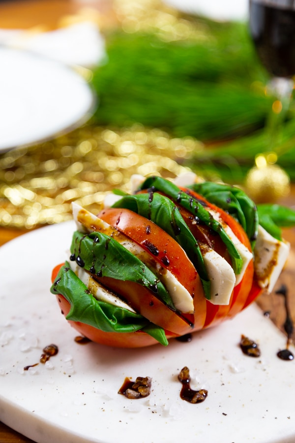A tomato sliced and stuffed with vegan mozzarella, basil leaves, and balsamic vinegar on a white plate with balsamic glaze drizzled on the plate