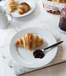 Croissants on white plates on a marble background with a white wood base with blueberry jam