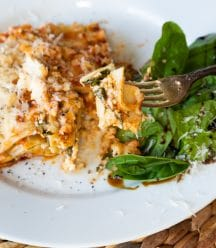 A slice of vegan spinach lasagna on a white plate with a side salad.