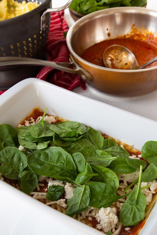 A layer of lasagna noodles, red sauce, vegan mozzarella and ricotta cheese, and baby spinach leaves in a white pan with a pan of sauce in the background.