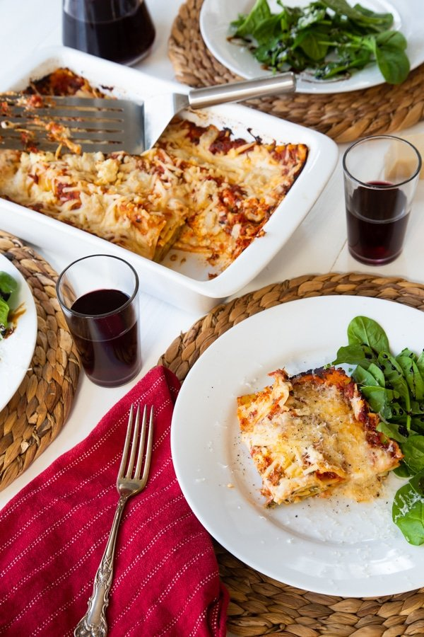 A slice of vegan spinach lasagna on a white plate with a side salad, and another plate of food on a wicker place mat and a white ceramic pan of lasagna in the background which happened to be the first recipe recreation of Veganosity.