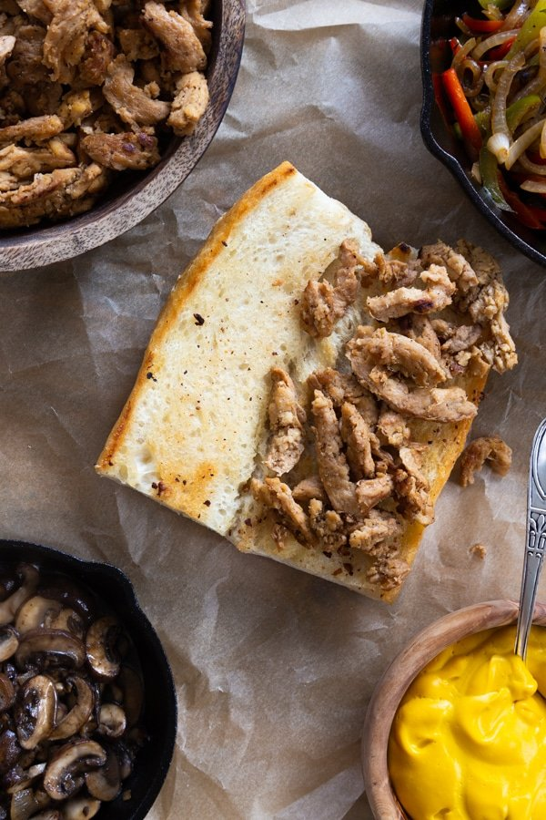 Building a philly cheesesteak process shot with soy curls and grilled bread