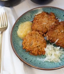 Potato pancakes with apple sauce and sauerkraut on a blue plate with a gold fork