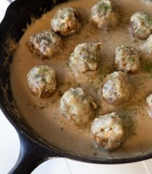 Vegan Swedish meatballs in gravy in a black cast-iron skillet on a white board.