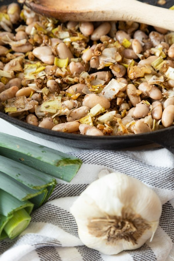 Sauteed leeks, garlic, walnuts, and white beans in a balsamic reduction in an iron skillet with a garlic bulb and leeks next to the pan