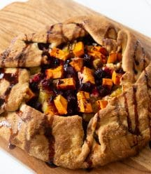 A roasted sweet potato and beet galette drizzled with a balsamic glaze on a wood cutting board