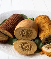 Three vegan turkey roasts on a white platter on greens, sliced on the ends showing the stuffing in the center