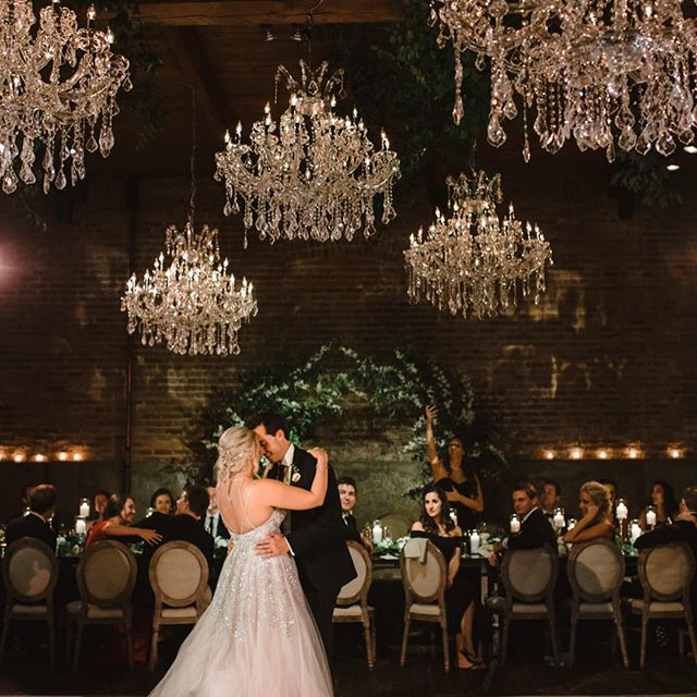 Alex and Max dancing at their wedding with chandeliers hanging over them and their bridal party sitting at a long table watching them