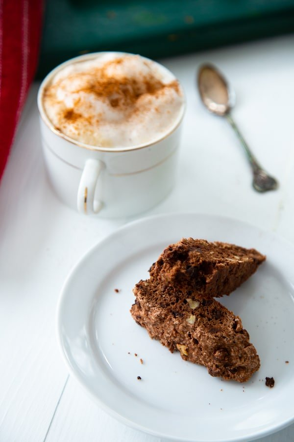 Two pieces of chocolate biscotti on a white plate with a cup of coffee and foamy milk sprinkled with cinnamon next to it and a small silver spoon next to the cup on a white table