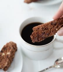 Chocolate chip and pecan biscotti being dipped into a cup of coffee in a white cup with a white plate of biscotti next to it and a silver spoon on the white wood table