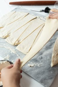vegan croissant dough in triangles being stretched over marble