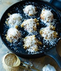An iron pan with roasted mushrooms covered in Parmesan and a gold measuring spoon full of breadcrumbs and garlic cloves next to it.