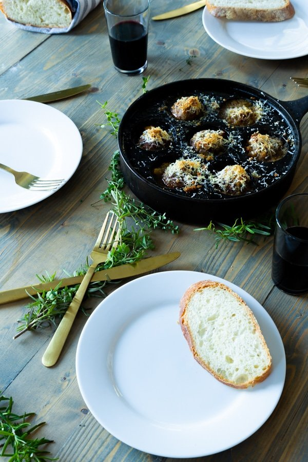 An iron skillet with roasted mushrooms and three white plates with a slice of bread and gold utensils, fresh herbs and glasses of wine around the pan.