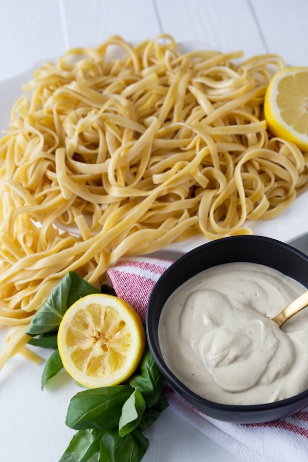 A platter of fettuccine and a bowl of Alfredo sauce with a gold spoon in the black bowl and lemon halves and fresh basil