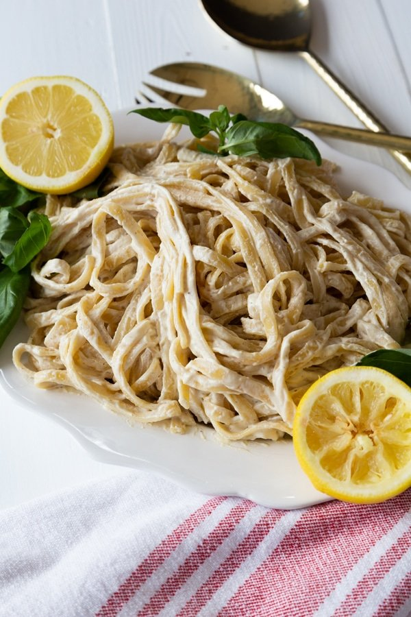 A white platter with vegan fettuccine Alfredo and lemon halves and fresh basil next to a red and white towel and gold serving utensils