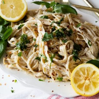 A white platter with vegan Fettuccine Alfredo sprinkled with fresh basil and two lemon halves on the edge of the plate
