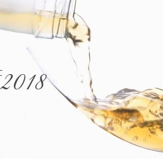 "White wine being poured into a glass and the text, ""Best of 2018"" in black on a white background"