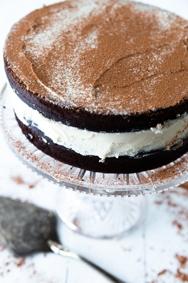 A chocolate cake with white frosting on a glass cake plate with a silver cake knife next to it.