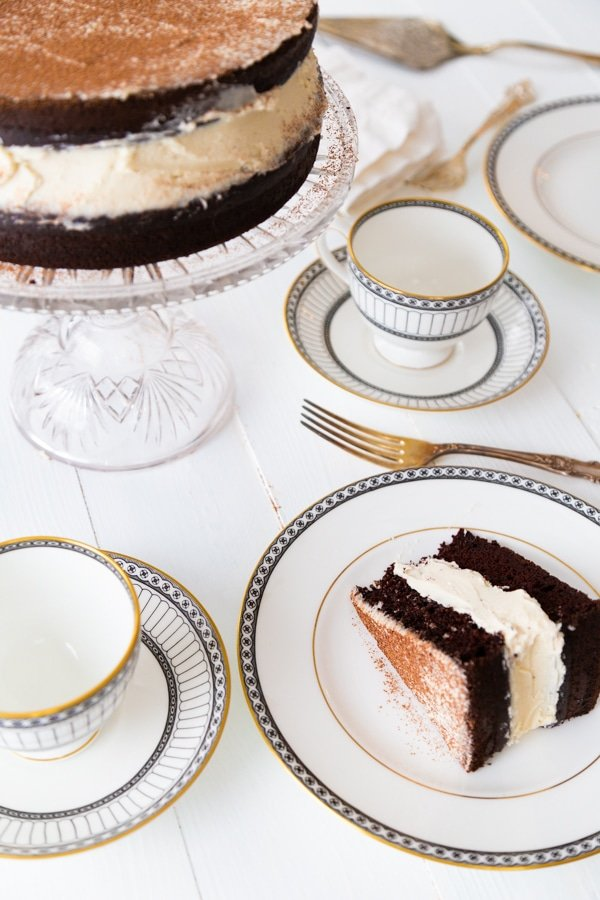 A chocolate cake on a glass cake stand and a white plate with a slice of the cake and empty tea cups next to the cake