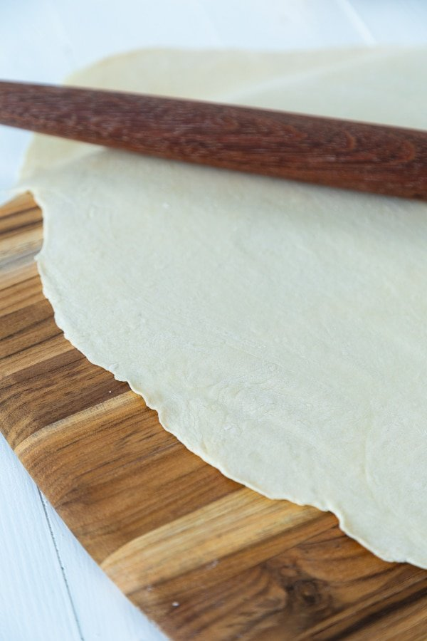 Pasta dough rolled out thin on a wood board with a wooden rolling pin
