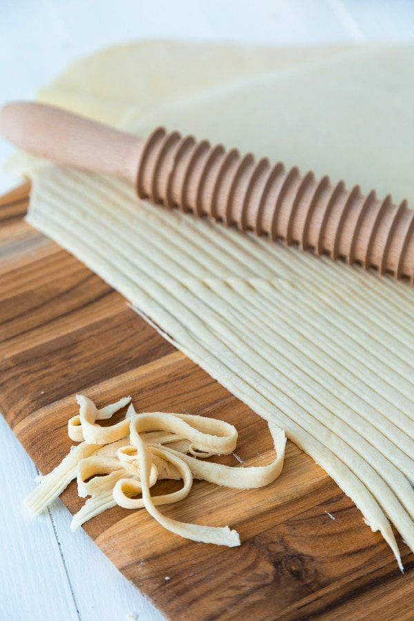 A wooden pasta cutting roller making noodles out of pasta dough