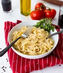 Pasta noodles in a white bowl with two forks and fresh herbs in the bowl, on a red striped napkin with whole tomatoes and two glasses of red wine and a bottle of olive oil in the background