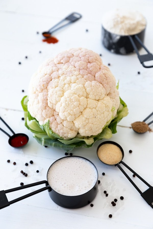 A whole cauliflower and assorted spices in black measuring cups and spoons on a white table.