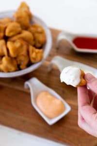 Veganosity's favorite recipe caulflower poppers being dipped in a vegan ranch sauce with a bowl of cauliflower poppers in the background with vegan ranch, vegan sriracha mayo, and vegan hot sauce in three separate white dishes on a wood board.