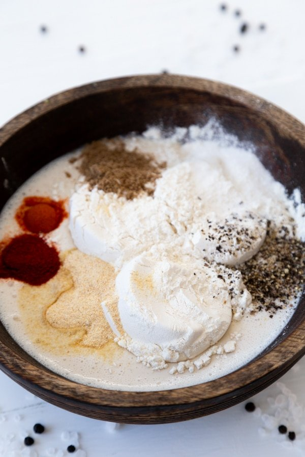 A wood bowl with milk, flour, and spices on a white table.