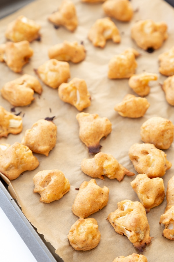 Baked cauliflower poppers on a parchment lined baking sheet.
